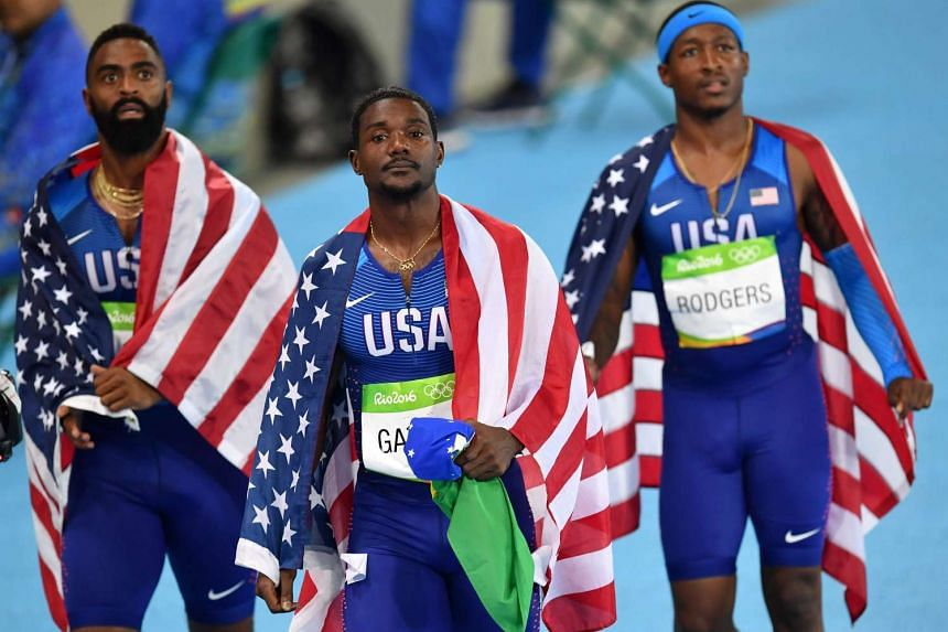 (LtoR) USA's Tyson Gay, USA's Justin Gatlin and USA's Michael Rodgers react after being disqualified of the Men's 4x100m Relay Final during the athletics event at the Rio 2016 Olympic Games at the Olympic Stadium in Rio de Janeiro on August 19.