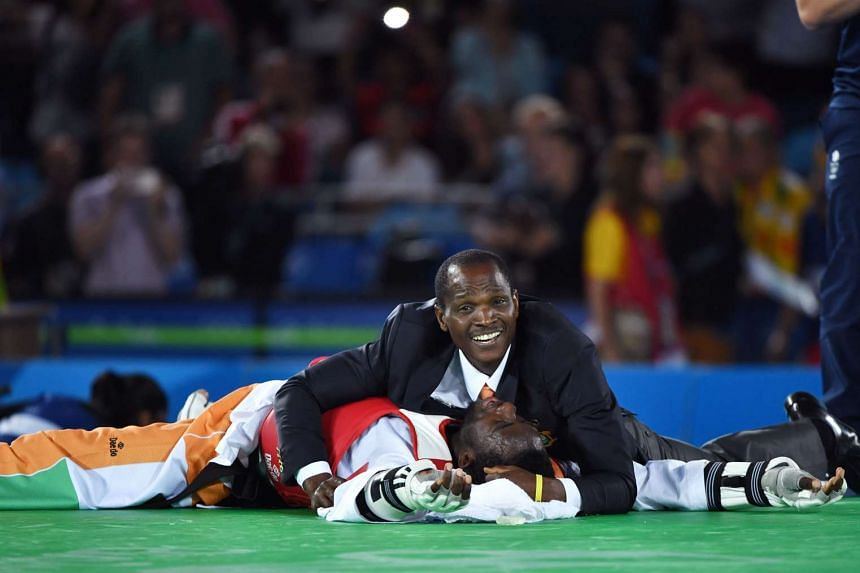 Ivory Coast's Cheick Sallah Junior Cisse (down) celebrates after winning the men's taekwondo gold medal bout in the -80kg category as part of the Rio 2016 Olympic Games, on August 19.