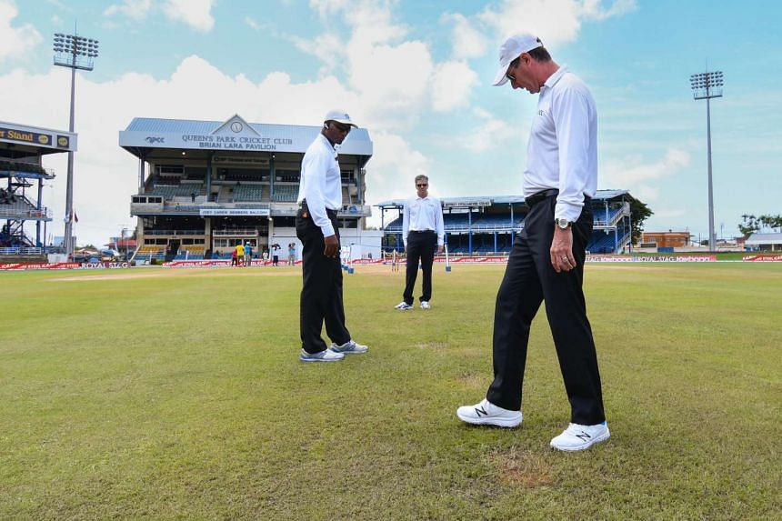 Umpire Rod Tucker (right) Nigel Llong (centre) and Gregory Brathwaite (left) inspect the pitch and out field during day 2 of the 4th and final Test between West Indies and India at Queen's Park Oval in Port of Spain, Trinidad on August 19.