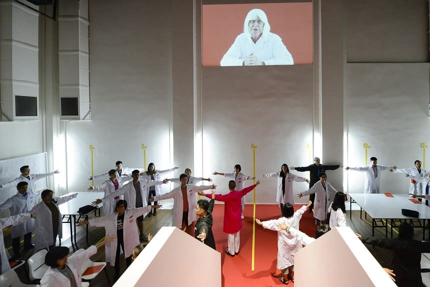 Participants in white laboratory coats are guided through exercises and tasks by facilitators in coloured coats.