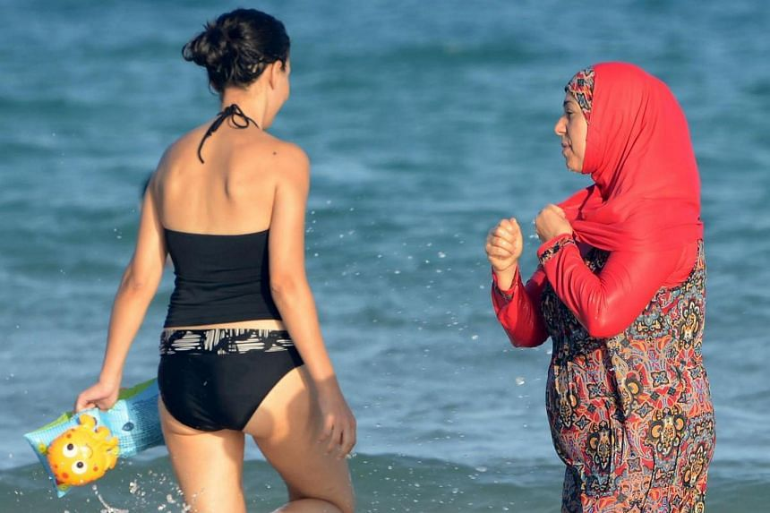 "This photo taken on August 16 shows Tunisian women, one (R) wearing a ""burkini"", a full-body swimsuit designed for Muslim women, walking in the water at Ghar El Melh beach near Bizerte, northeast of the capital Tunis."