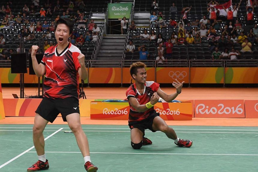 Indonesia's gold medalists Liliyana Natsir (left) and Tontowi Ahmad react after winning their mixed doubles badminton final.