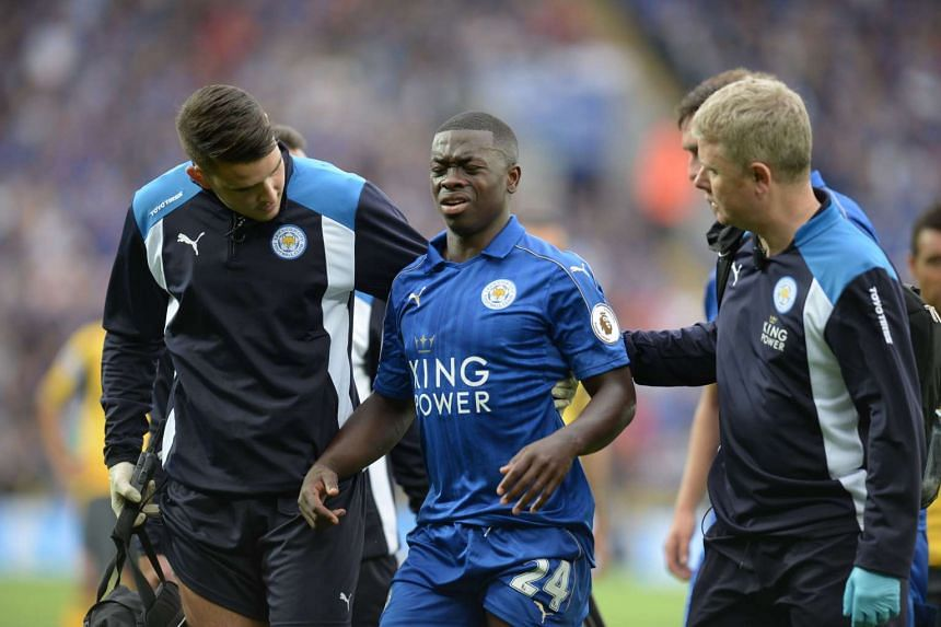 Leicester City's French midfielder Nampalys Mendy (C) is helped off the pitch after getting injured.