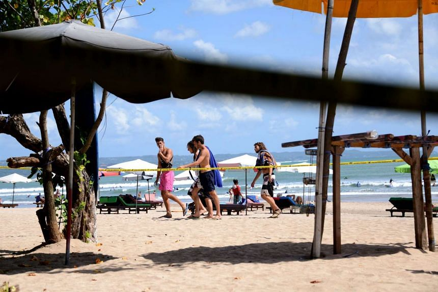 Foreign tourists walk past the site where a policeman was killed several days ago near Kuta beach on Indonesia's resort island of Bali on Aug 19, 2016.