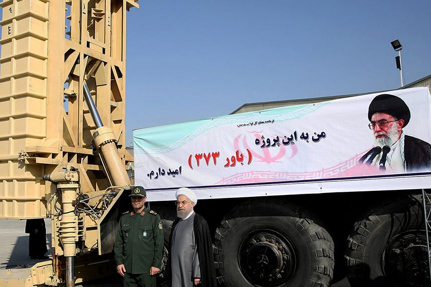 Iranian President Hassan Rouhani (centre) and Iranian Defence Minister Hossein Dehghan (left) standing next to the new Bavar 373 missile defence system in Teheran.