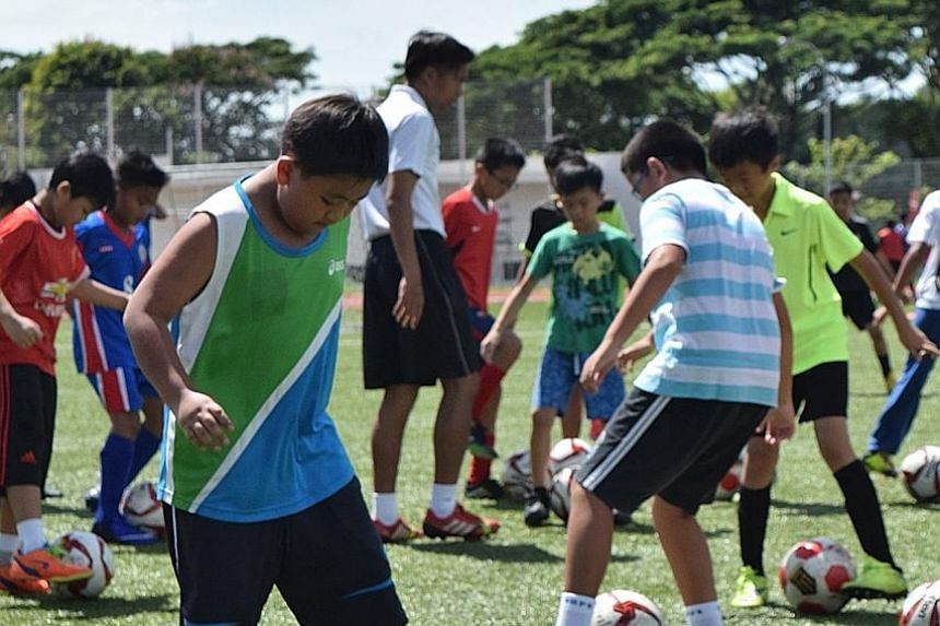 Boys being put through basic football drills yesterday at a clinic jointly organised by Fandi Ahmad's F-17 Academy and the Dyslexia Association of Singapore (DAS). The session, aimed at developing the students' football skills, was conducted at the S