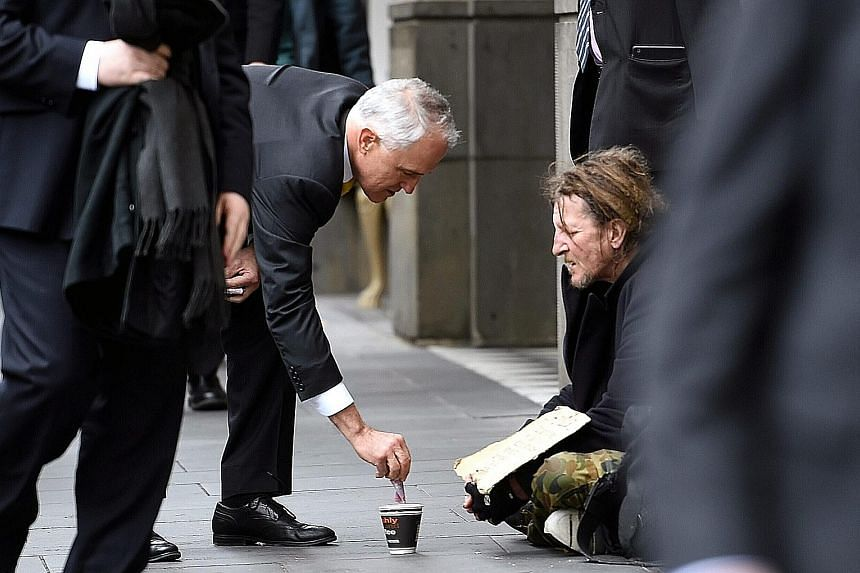 Mr Turnbull's act of depositing a $5 note into the cup of a homeless man has led to criticism from social media users and in the news media.