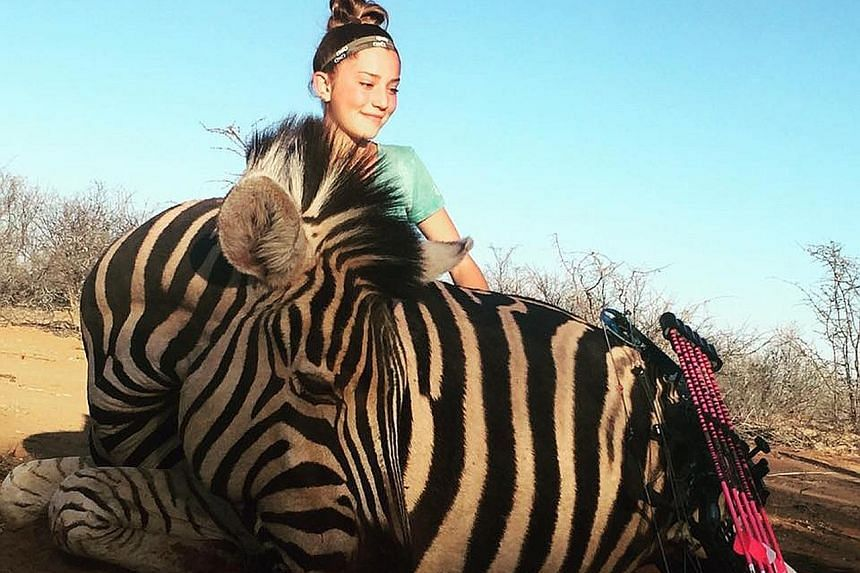 Aryanna's photos of her posing with a giraffe and zebra that she killed during a hunting trip in South Africa have ignited a firestorm on social media, with one commenter hoping that she will be killed by animals. With her and the dead giraffe is Mr