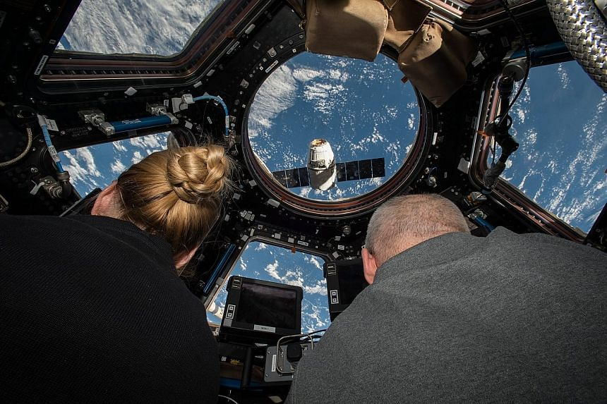 Astronauts Kate Rubins and Jeff Williams preparing to grapple the SpaceX Dragon supply spacecraft from aboard the ISS, which will operate until at least 2024. The pair also installed the first of two new docking adapters during a spacewalk on Friday.