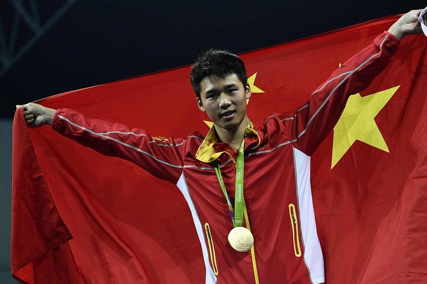 Gold medallist China's Chen Aisen poses during the podium ceremony of the men's 10m platform final during the diving event.