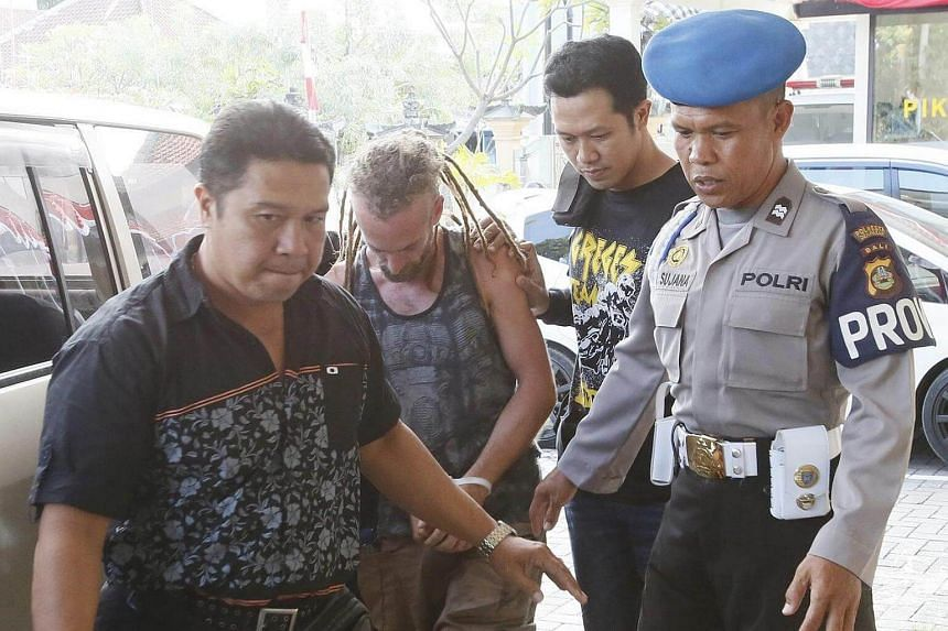 British national David Taylor is escorted by police officers as he was arrested over the alleged murder of a police officer in Bali.