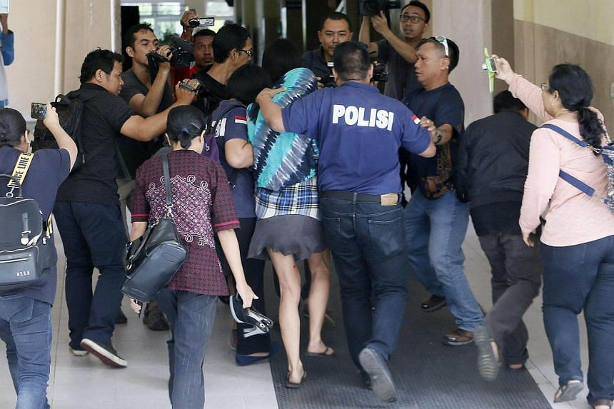 Australian Sara Connor (centre) is escorted by police officers as she was arrested over the alleged murder of a police officer in Bali.