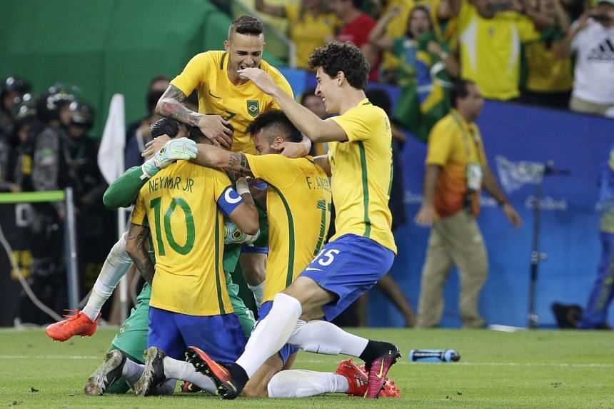 Neymar of Brazil mobbed by teammates after scoring the deciding penalty in the shootout on Aug 20.