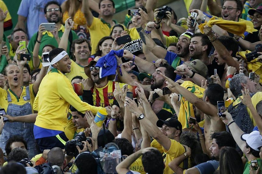 Neymar of Brazil celebrating with fans in the stands after defeating Germany in the football men's gold medal match.