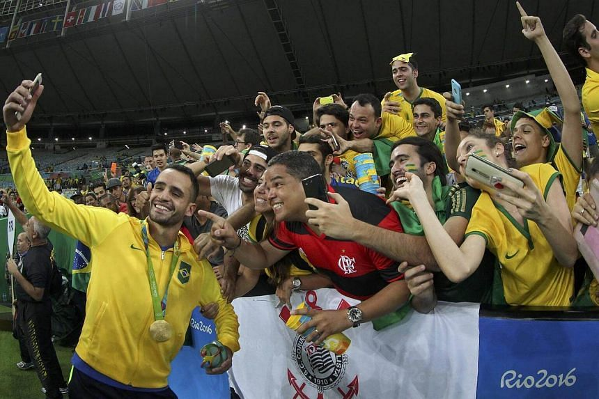 Renato Augusto of Brazil celebrates by taking a selfie with fans after Brazil defeated Germany.