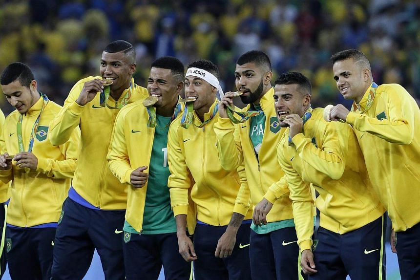The Brazilian football team with their gold medals strike a pose for the Maracana crowd.