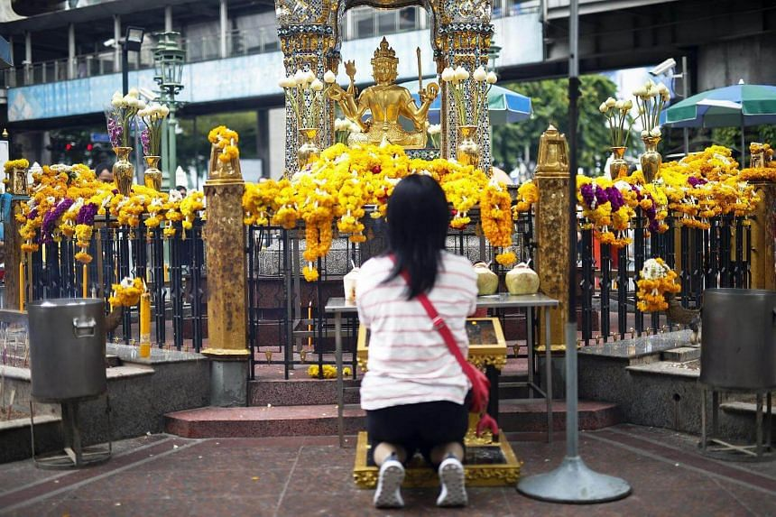 A devotee worships a statue of Lord Brahma ahead of the one year anniversary of the deadly bomb blast at the Erawan Shrine in Bangkok, Thailand on August 16.