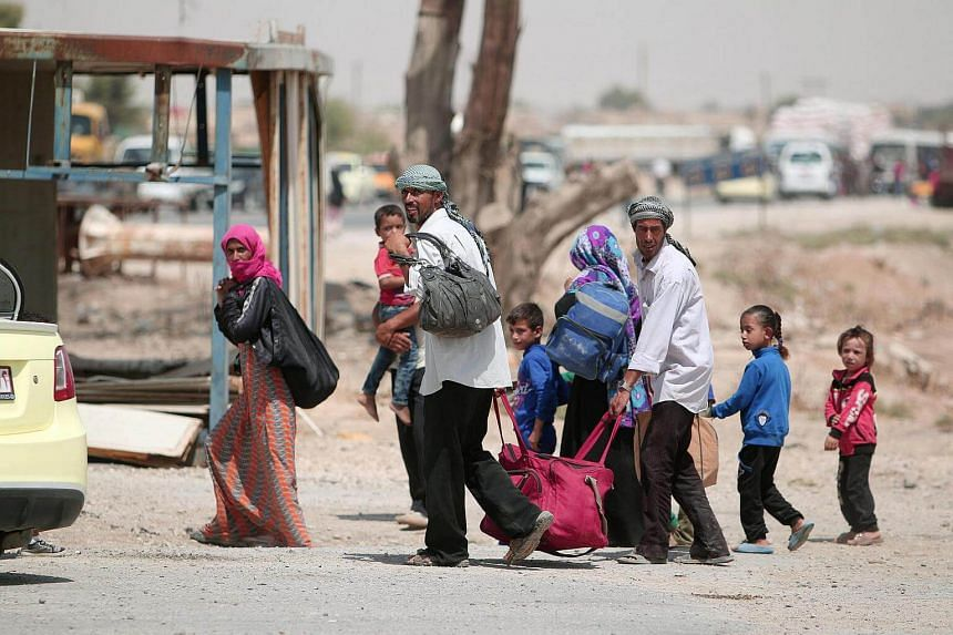 People fleeing Hasaka after the Syrian government deployed warplanes to bomb the Kurdish-held areas in the city on August 20.