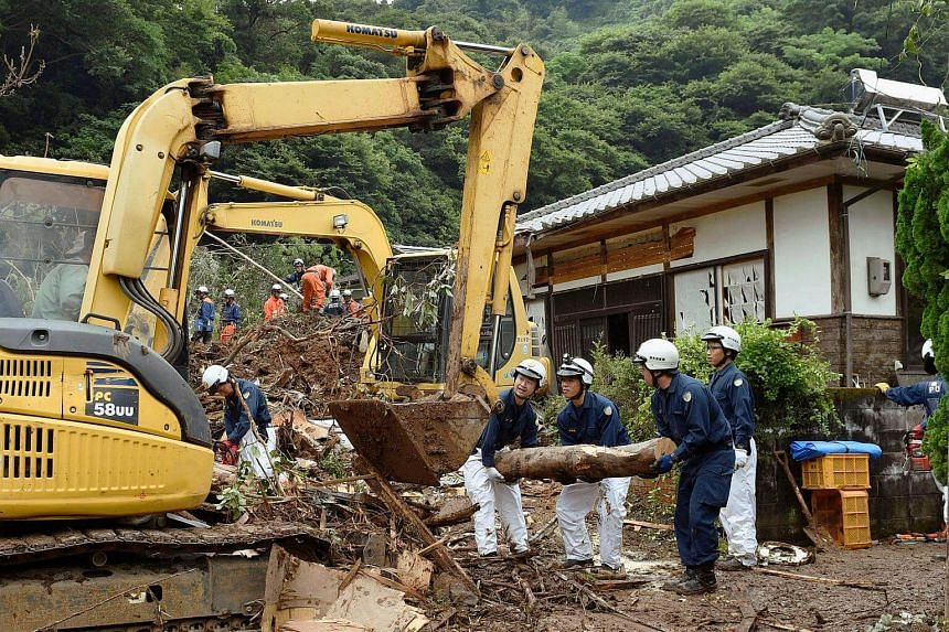 Rescue team members conduct search and rescue operations at a landslide site caused by heavy rain in Uto, Kumamoto prefecture, Japan on 21 June.