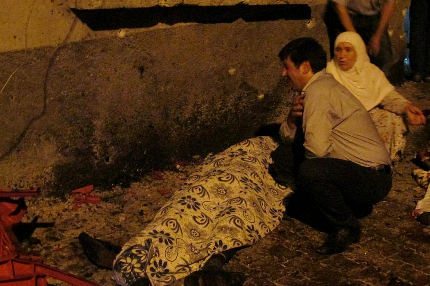 A man and a woman mourn next to a body of one the victims of a blast targeting a wedding ceremony in the southern Turkish city of Gaziantep, Turkey, on August 20.