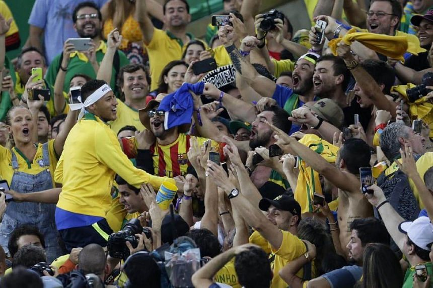 Brazil's captain Neymar jumps into the crowd to celebrate the football team's Olympic gold medal.