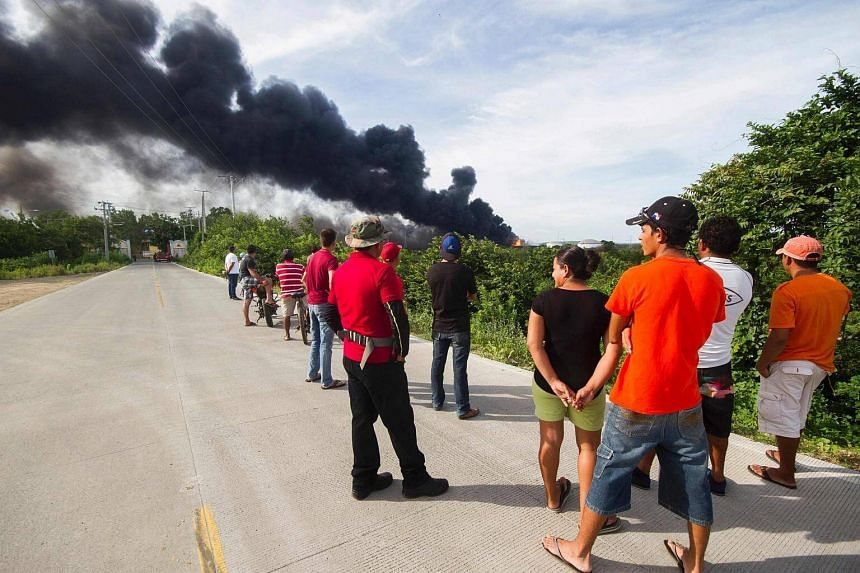 Locals stare at the fire following the explosion of a second fuel storage tank at the Puma Energy plant in Puerto Sandino on August 18.