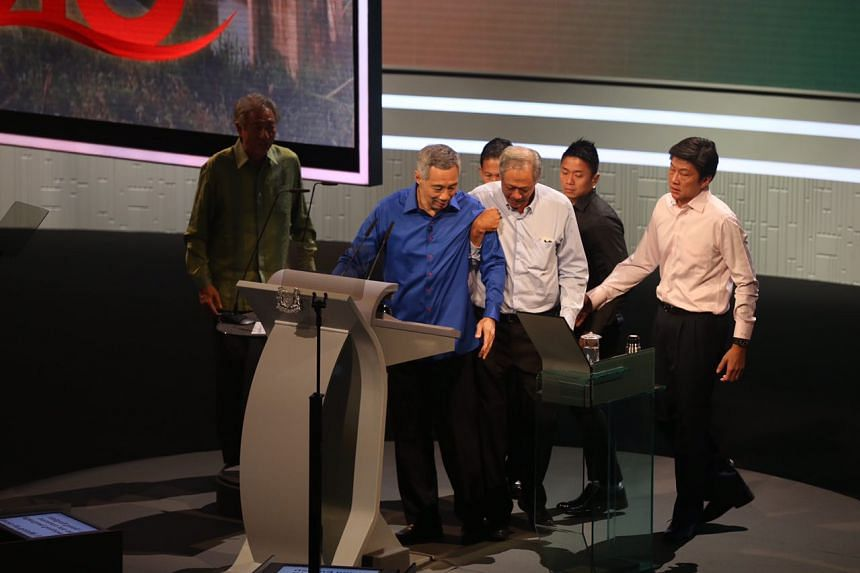 Prime Minister Lee Hsien Loong being helped by Defence Minister Ng Eng Hen after he suddenly felt unwell during the National Day Rally on Aug 21, 2016.
