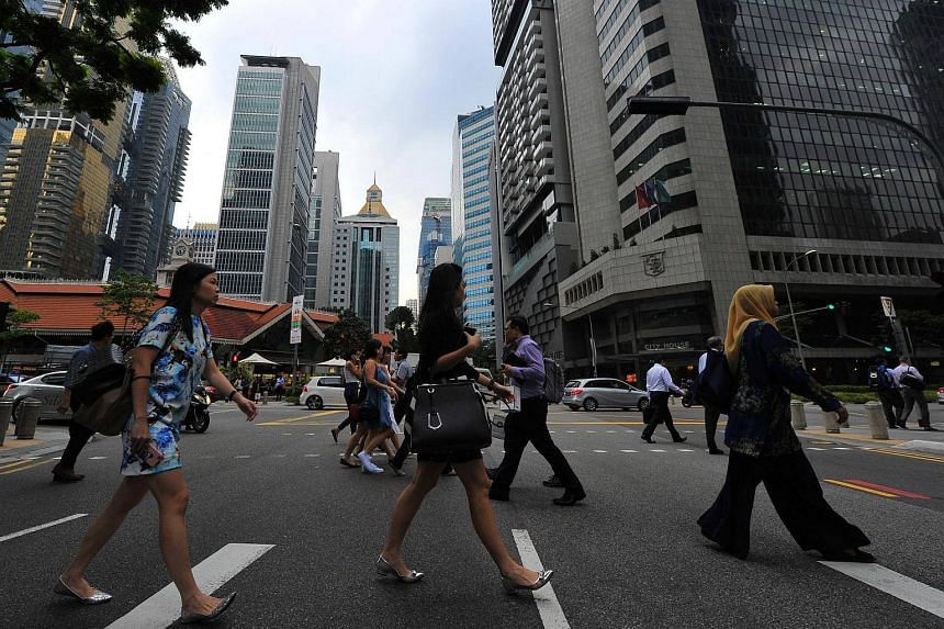 Office workers crossing the road at Robinson Road in the Central Business District on March 24.
