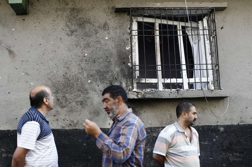 People stand below a shattered window that was damaged during a bomb attack on a wedding party the day before, on Aug 22, 2016, at a street in Gaziantep.