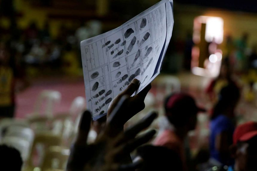 A drug user holds up a copy of his fingerprints, after more than 1000 residents surrendered to officials in the Philippines.