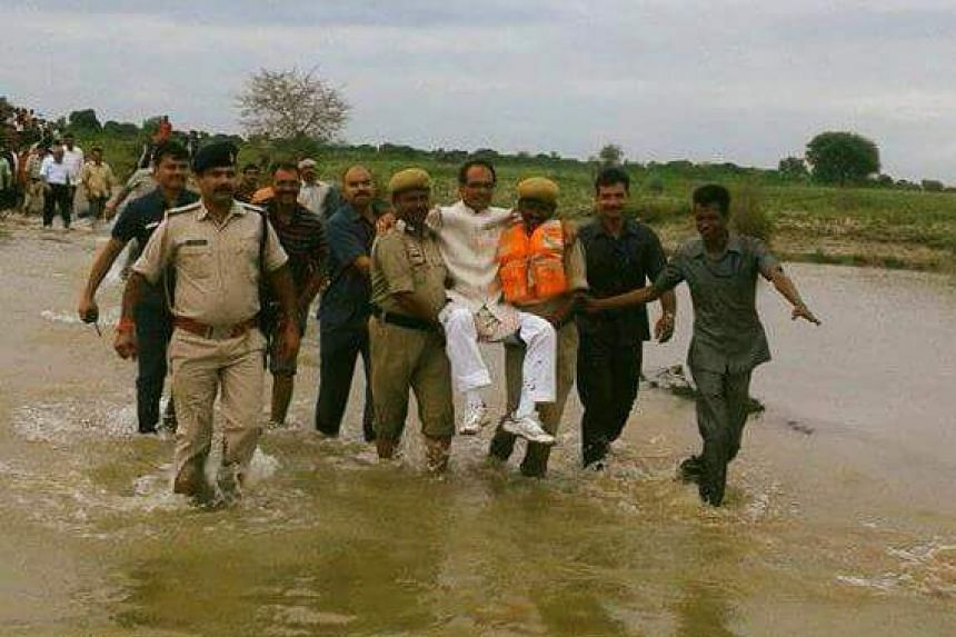 Shivraj Singh Chouhan being carried through water in a field.