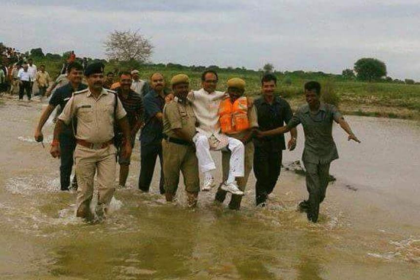 Shivraj Singh Chouhan being carried through water in a field.