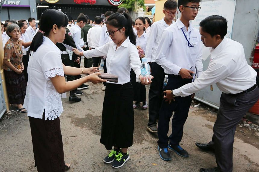 Cambodian officials search for cheat sheets prior to a Grade 12 exam at a school in Phnom Penh, Cambodia, on Aug 22, 2016.