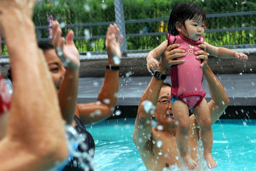 A sing-and-swim lesson for toddlers at a swim school.