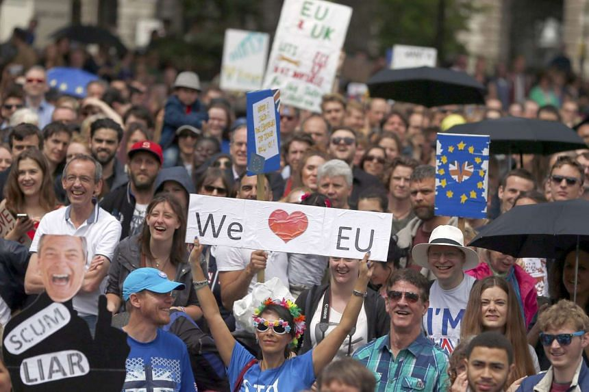 People hold banners during a demonstration against Britain's decision to leave the EU, in Parliament Square, in central London, Britain July 2.