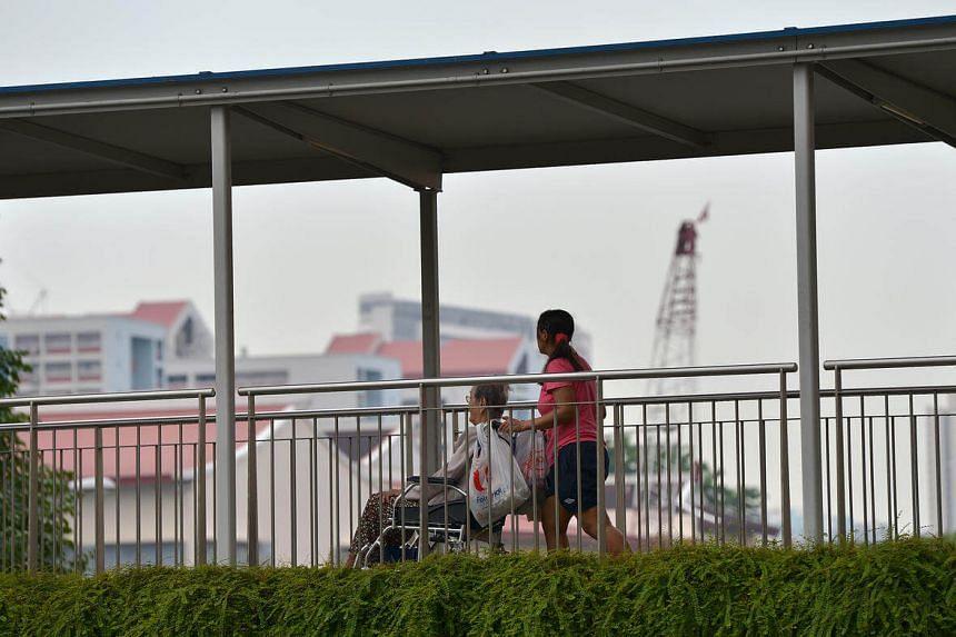 A domestic helper and an elderly in a wheelchair seen at a pedestrian overhead bridge.