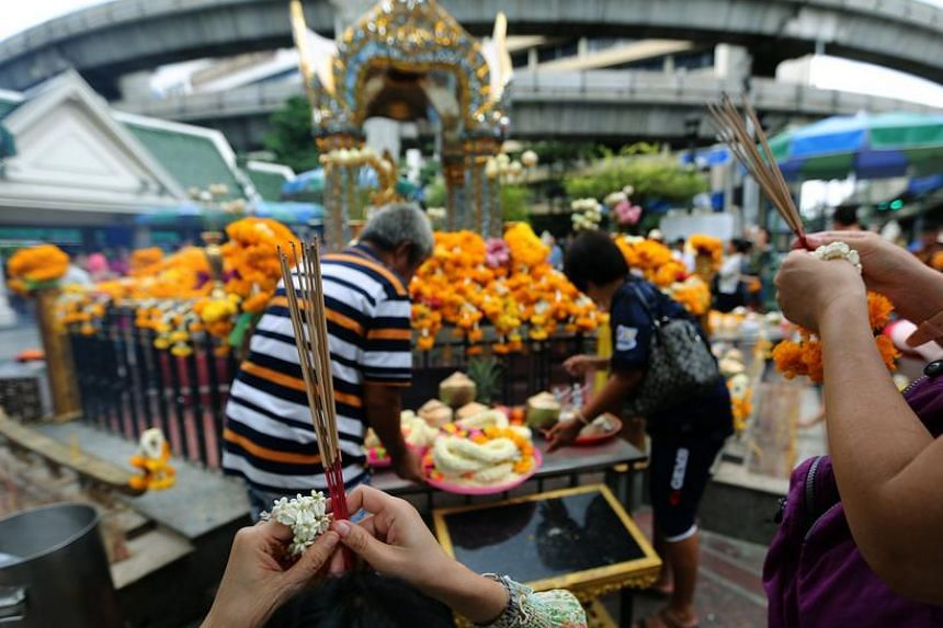 Thai and foreign devotees worship Lord Brahma, the Hindu god of creation, on the one-year anniversary of a deadly bomb blast at the Erawan Shrine in Bangkok, on Aug 17, 2016.