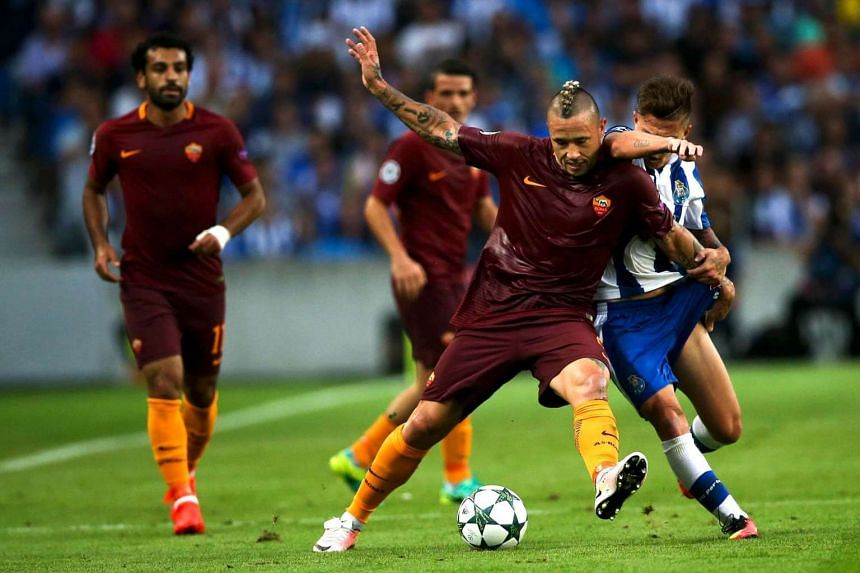FC Porto's Otavio (right) vies for the ball with Roma's Radja Nainggolan (left) during their UEFA Champions League Play off First Leg match held at Dragao stadium in Porto, Portugal, on August 17.