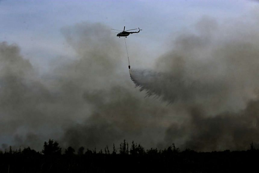 A helicopter from the Indonesian National Disaster Management agency drops water on a fire in Ogan Ilir, near Palembang, South Sumatra, Indonesia, August 11.