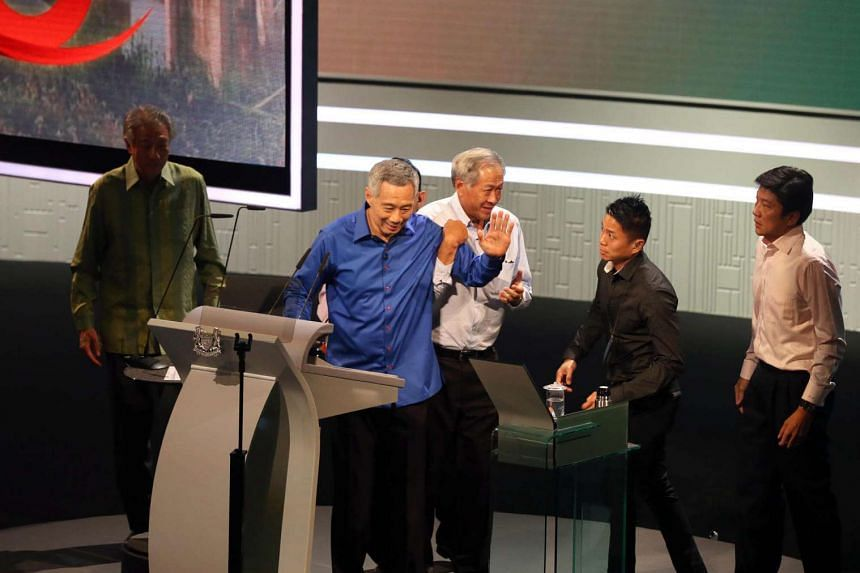 PM Lee Hsien Loong being helped off the stage when he was delivering his speech at the National Day Rally 2016 at ITE College Central. He later returned to finish his speech.