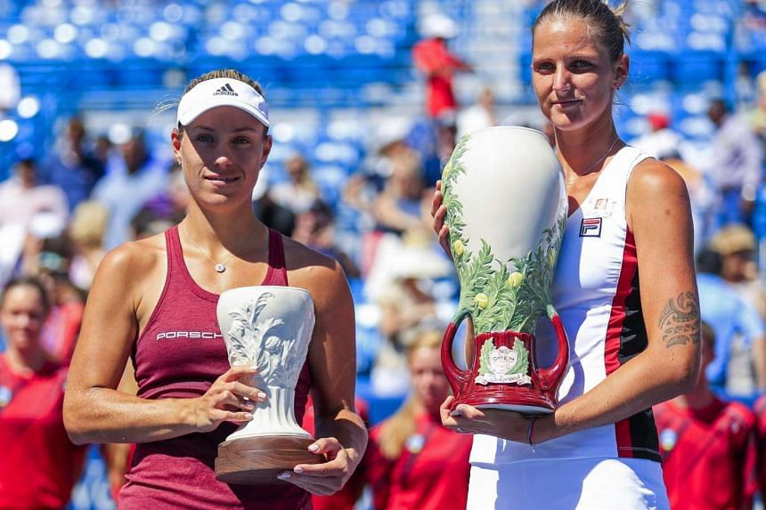 Karolina Pliskova (right) holds the Rookwood Cup as she poses with Angelique Kerber (left) after defeating her in the final of the Western & Southern Open tennis championships at the Linder Family Tennis Center on Aug 21.