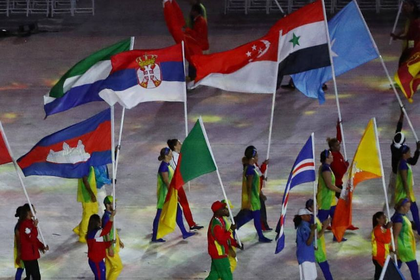 Flagbearer Griselda Khng of Singapore (centre) walks in with the Singapore flag at the Rio Olympics closing ceremony.