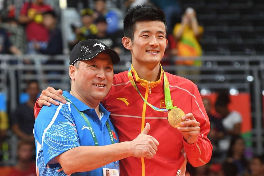 China's Chen Long (right) holds his gold medal as he poses with China's national badminton coach Li Yongbo on Aug 20, 2016.