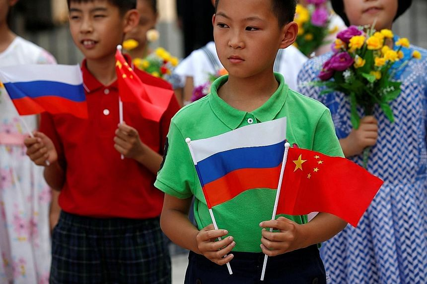 Children with Russian and Chinese flags before a welcoming ceremony for Russian President Vladimir Putin in Beijing in June. Analysts say that rather than a Cold War-style confrontation, what is happening instead is a deepening of the Sino-Russian re