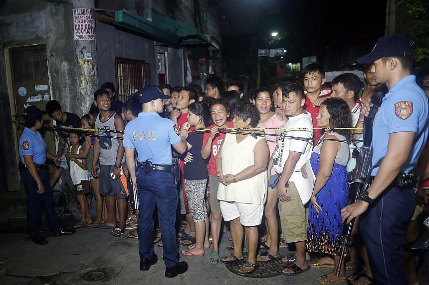People standing behind a police line at the scene of a police operation against illegal drugs that resulted in the killing of an alleged drug dealer in Manila last Friday.