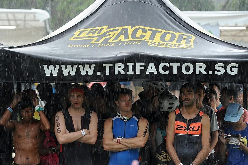 Participants taking shelter under a tent, as they wait for the race to resume following yesterday morning's heavy downpour, which halted the race for nearly three hours before it was restarted at 10.20am.