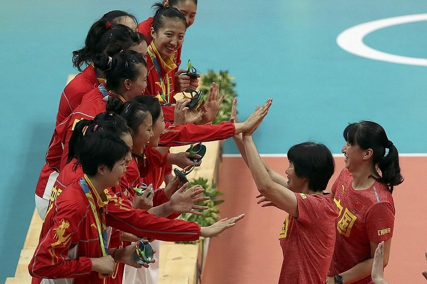 China's gold-winning volleyballers celebrating their triumph with coach Lang Ping and her assistant Lai Yawen (right). The volleyball players were one of a few bright spots of a Chinese Olympic contingent that won their fewest gold medals since the A