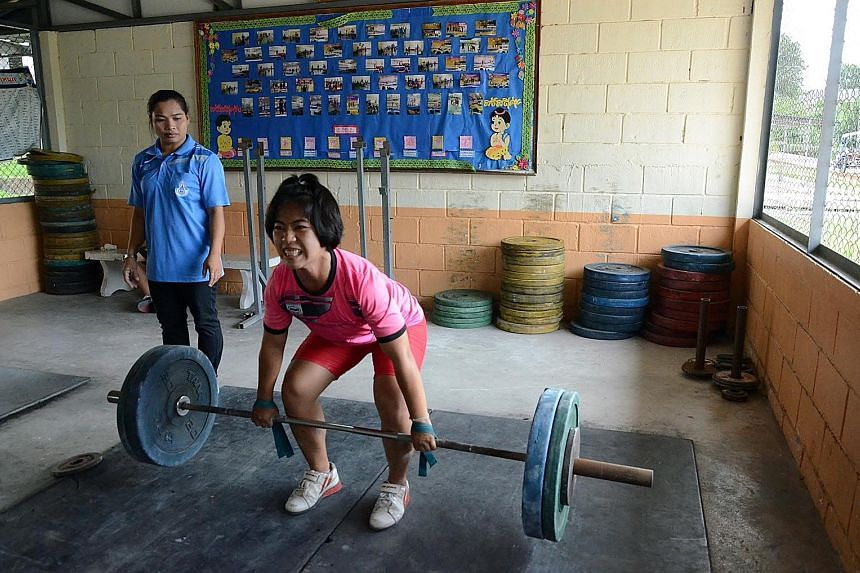 Coach Wandee Kameaim, the 58kg bronze medallist in Athens, looks on as her charge Supatcha Hadsadong trains in Suksa Songkro school's gym. Weightlifting is a way out of poverty for some Thai children.