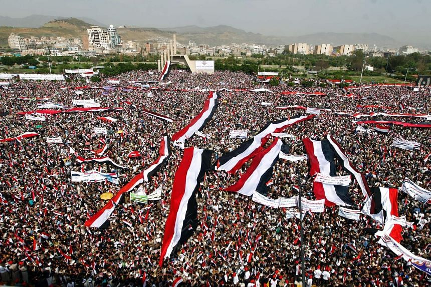Houthi demonstrators waving Yemeni flags and chanting slogans in Sanaa's Sabeen Square on Saturday. The demonstration - one of the biggest in Yemen since the civil war broke out last year - took place as a Saudi-led coalition backing exiled President