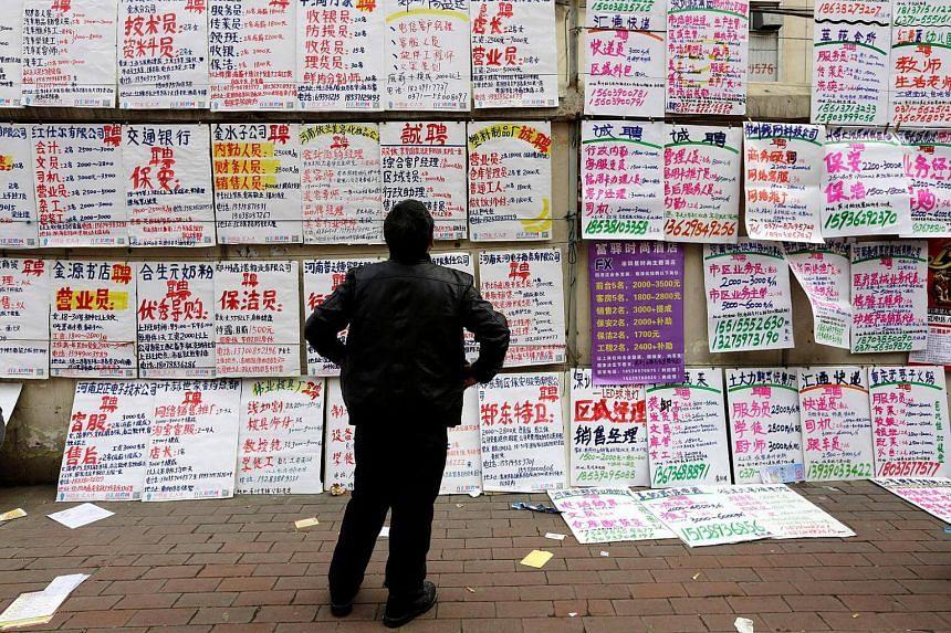 A man looks at job information at an employment fair beside a street in Zhengzhou, Henan province, Feb 19, 2014.